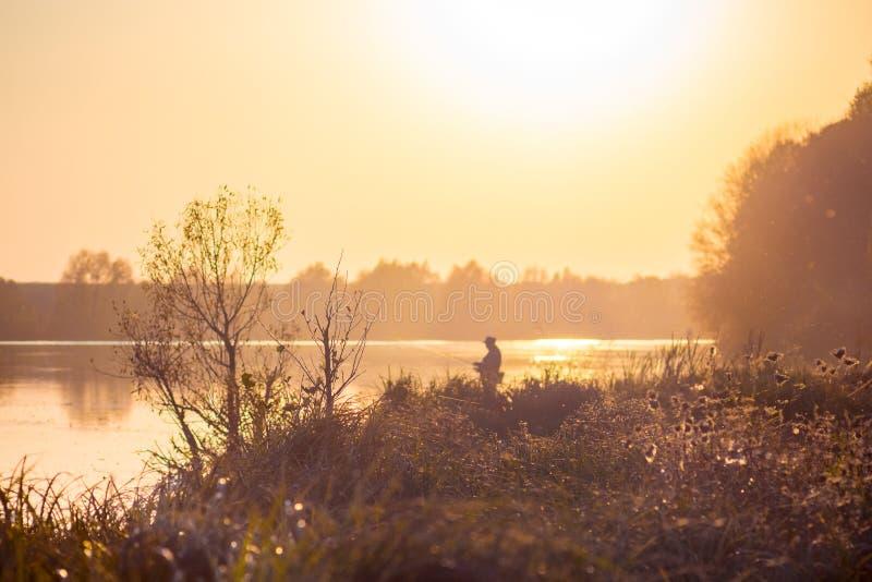 Paisaje con el pescador en la orilla del río durante la puesta del sol en tones_ anaranjado-marrón caliente fotos de archivo