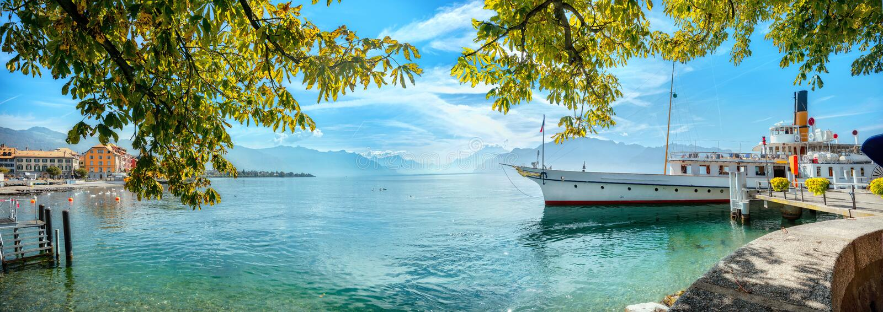 Paisaje con embarcadero y antiguo ferry turístico en el lago Geneva en la ciudad de Vevey. Cant?n de Vaud, Suiza imagen de archivo libre de regalías