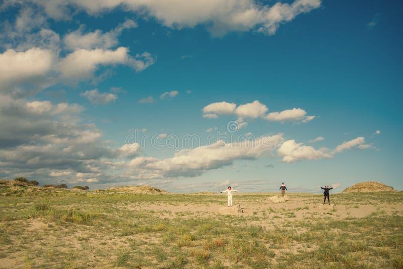Paisaje con la gente Tres personas que se colocan en un campo en las rocas con los brazos aumentados foto de archivo