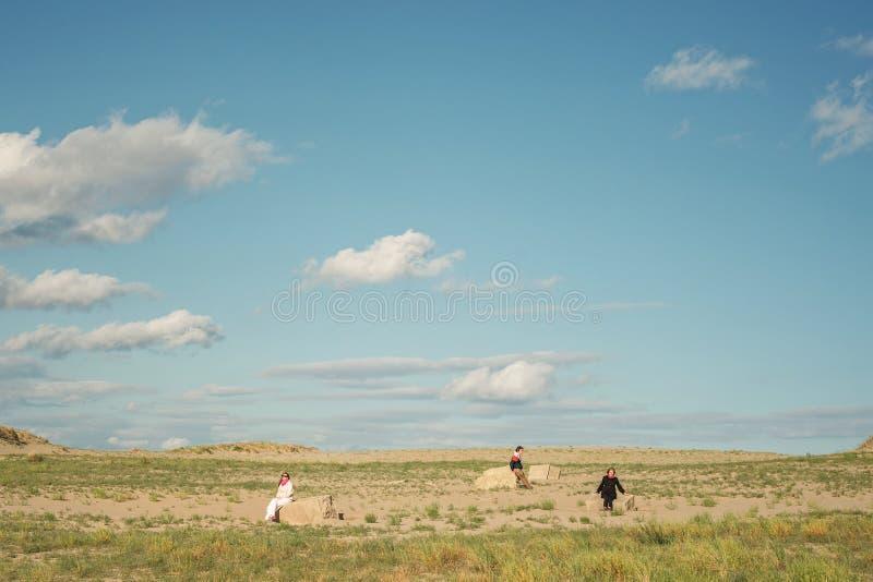 Paisaje con la gente Tres personas que se sientan en un campo en las rocas foto de archivo libre de regalías