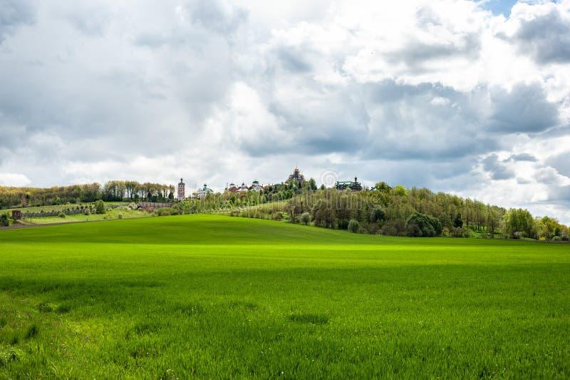 Paisaje con la hierba verde, los árboles y el monasterio encima de la colina debajo del cielo nublado fotografía de archivo