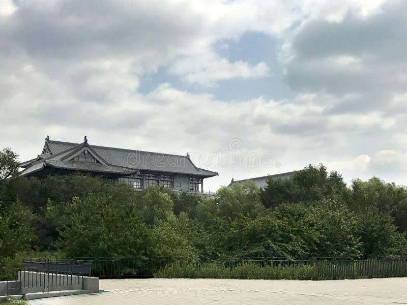 Paisaje con la pagoda antigua, los ?rboles y las nubes dram?ticas en las tierras mojadas de Changchun, China E imagenes de archivo