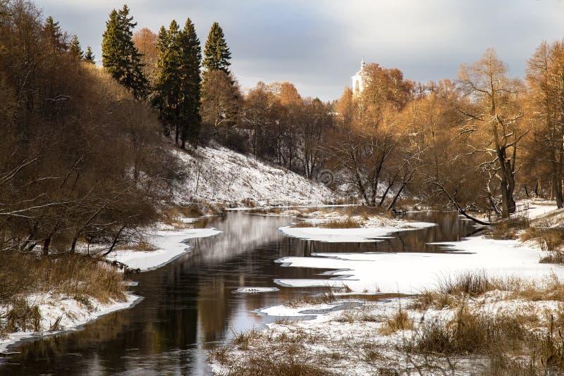 Paisaje con los árboles del otoño y el río nevoso imagen de archivo