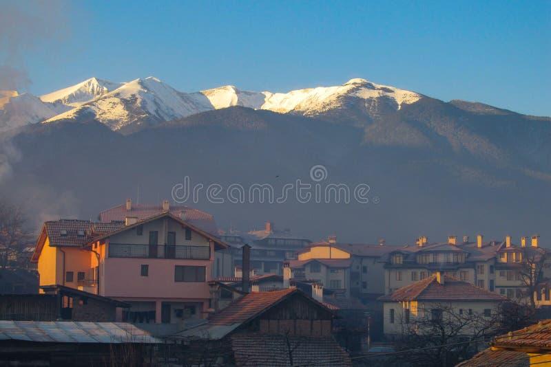 Paisaje con opiniones de la casa y montañas hermosas en la puesta del sol en Bansko, Bulgaria imagenes de archivo