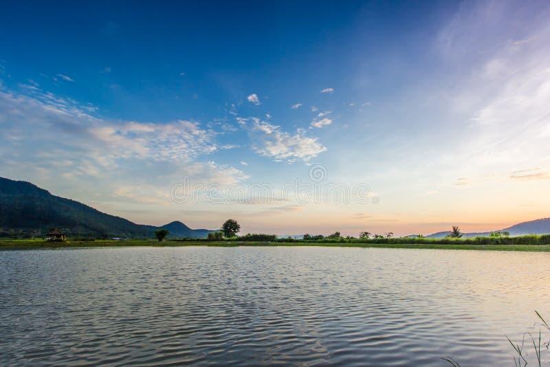 Paisaje con puesta del sol sobre el lago foto de archivo libre de regalías