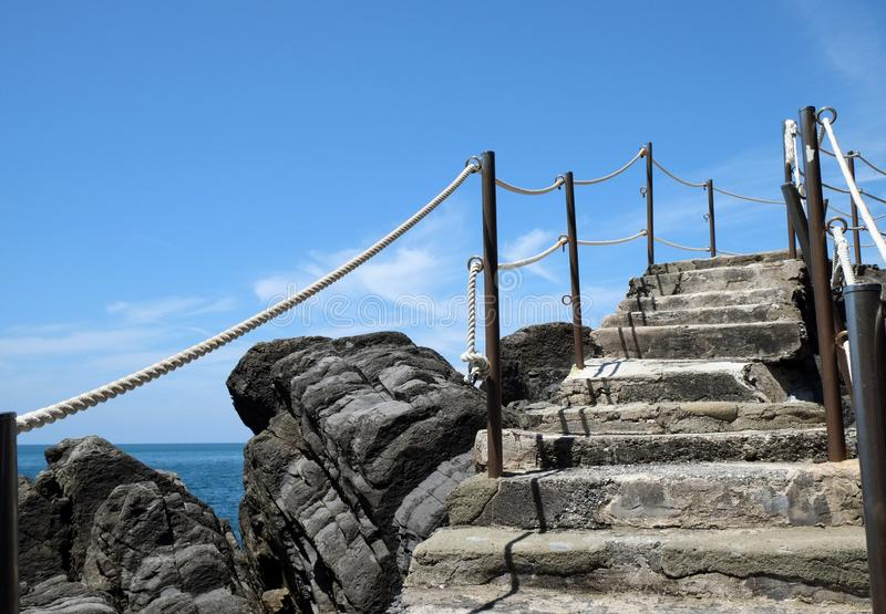 Paisaje con una escalera antigua en medio de piedras por el mar foto de archivo
