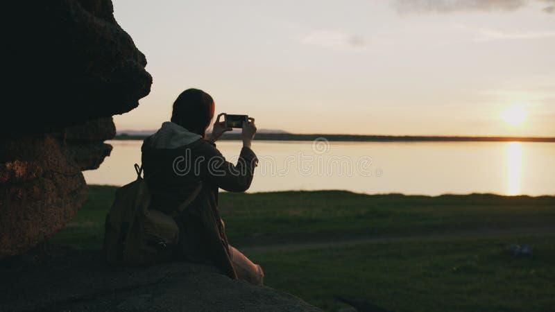 Paisaje de fotografía del backpacker turístico joven de la mujer en su cámara del smartphone después de caminar en roca en la pue fotos de archivo libres de regalías