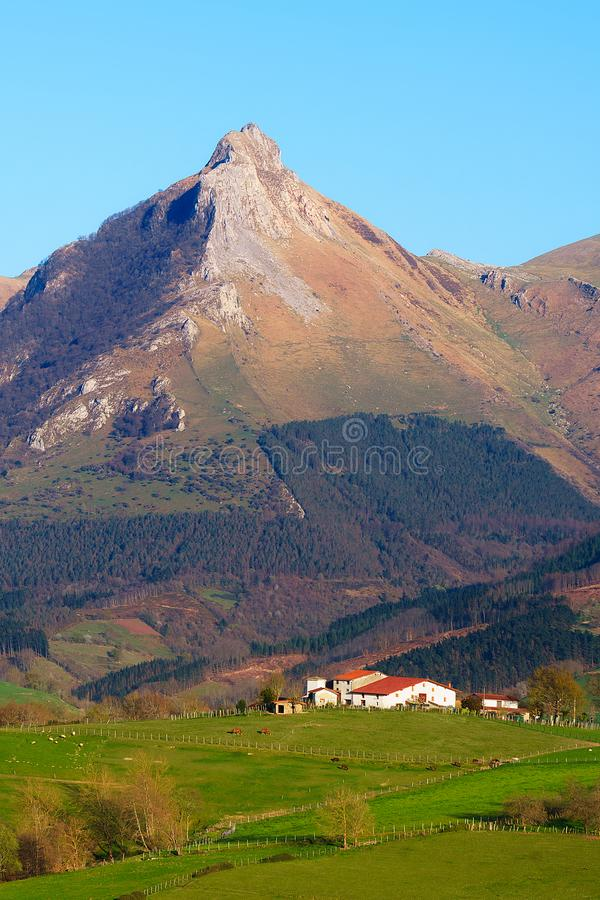 paisaje de granjas en Lazkaomendi en Gipuzkoa con la montaña de Txindoki imagen de archivo libre de regalías