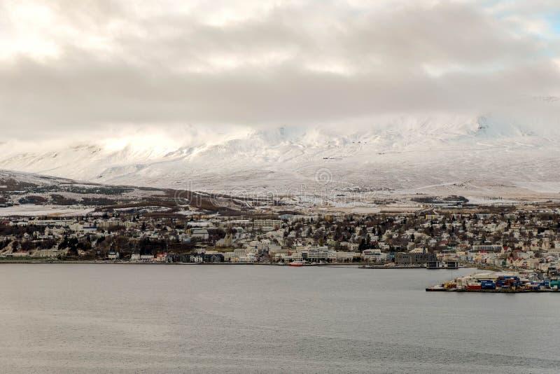 Paisaje de la ciudad de Akureyri de Islandia septentrional con la montaña del océano y de la nieve fotografía de archivo