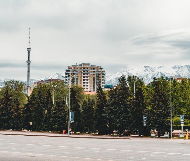 Paisaje de la ciudad de Almaty con las montañas coronadas de nieve de Tian Shan del tobe del kok en Almaty Kazajistán foto de archivo
