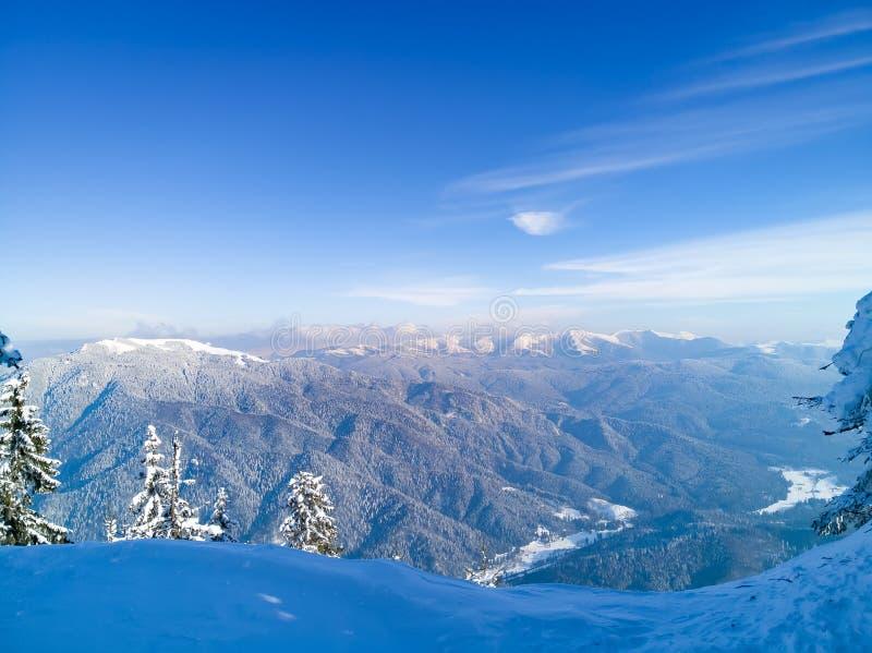 Paisaje de la escena del invierno con las montañas cubiertas en nieve Fondo listo de la Navidad con el cielo azul profundo bueno  foto de archivo
