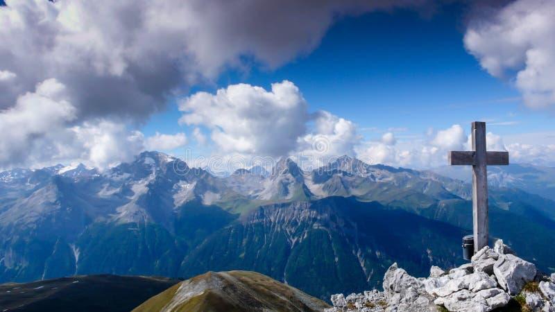 Paisaje de la montaña con una cruz en la cumbre y una gran visión detrás fotos de archivo