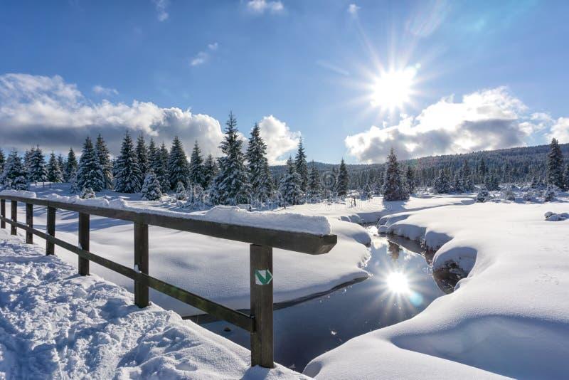 Paisaje de la montaña del invierno con la corriente y el puente de madera fotografía de archivo libre de regalías