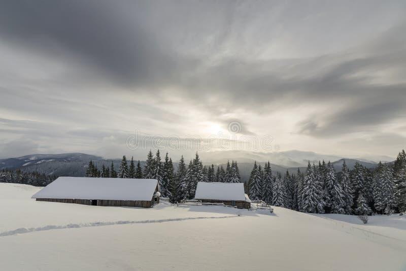 Paisaje de la monta?a del invierno Casas de madera viejas en el claro nevoso en el fondo del canto de la montaña, del bosque de l fotografía de archivo