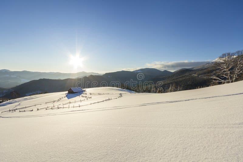 Paisaje de la Navidad del invierno del valle de la montaña en día soleado escarchado Choza abandonada de madera vieja del pastor  foto de archivo