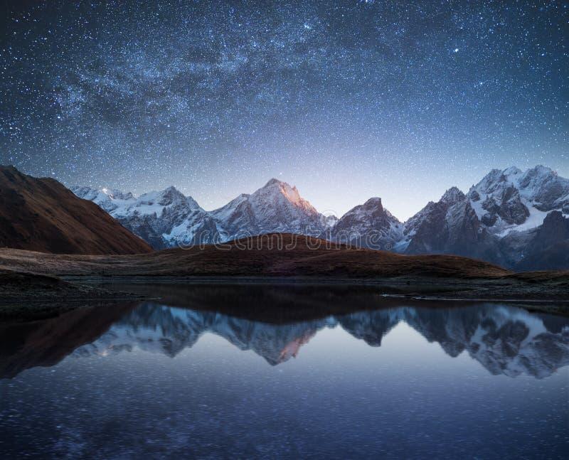 Paisaje de la noche con un lago de la montaña y un cielo estrellado fotos de archivo