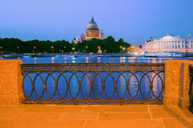 Paisaje de la noche con vistas al parapeto del granito, a Neva River y a catedral del St Isaac foto de archivo