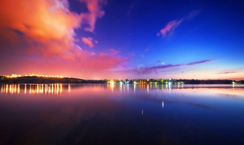 Paisaje de la noche en el lago con el cielo azul y las nubes fotos de archivo