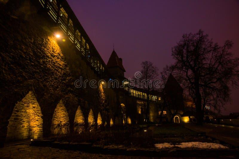 Paisaje de la noche de las paredes de la fortaleza con la iluminación La torre anterior Neitsitorn de la prisión en Tallinn vieja foto de archivo