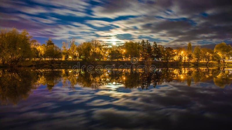 Paisaje de la noche sobre el río con los árboles encendidos por las luces y las nubes de la ciudad en el movimiento imágenes de archivo libres de regalías