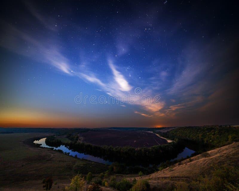 Paisaje de la orilla del verano en la noche estrellada con las nubes púrpuras imagen de archivo libre de regalías