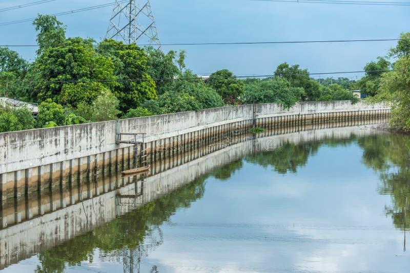 Paisaje de la pared de la protección contra inundaciones con reflexiones de madera de los barcos imagenes de archivo