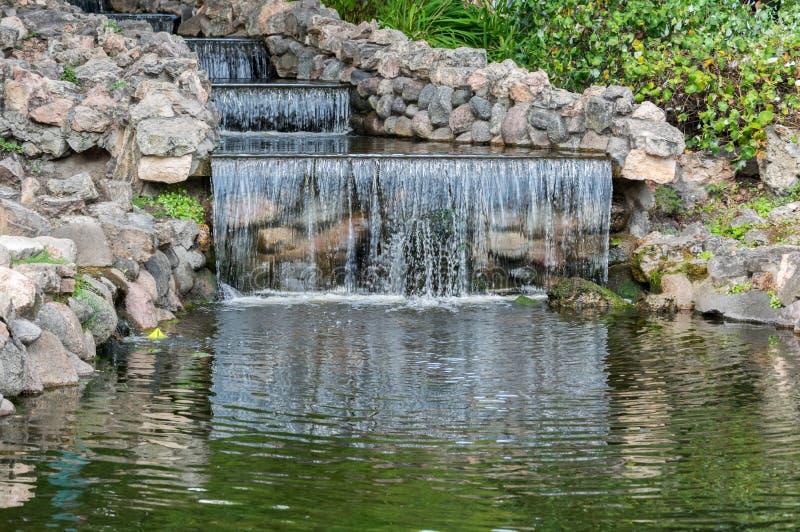 Paisaje de la pequeña cascada en el parque de la ciudad imágenes de archivo libres de regalías
