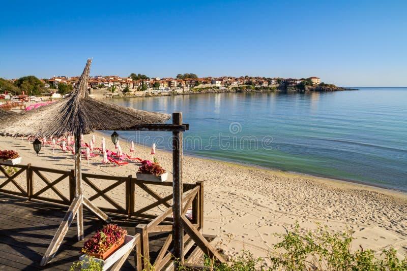 Paisaje de la playa - vista del café y de la playa arenosa con los paraguas y los ociosos del sol en la ciudad de Sozopol fotografía de archivo