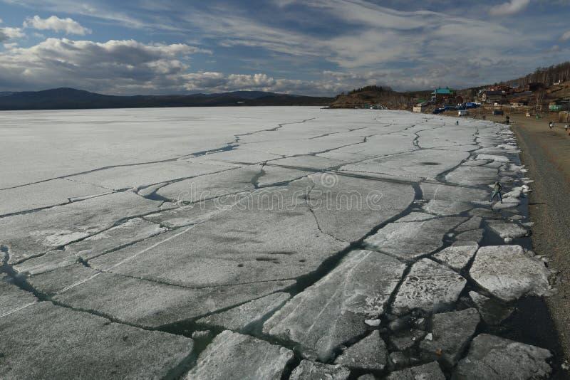 Paisaje de la primavera con la deriva del hielo en el lago y los ciclistas y la gente que montan a lo largo de él imagen de archivo libre de regalías