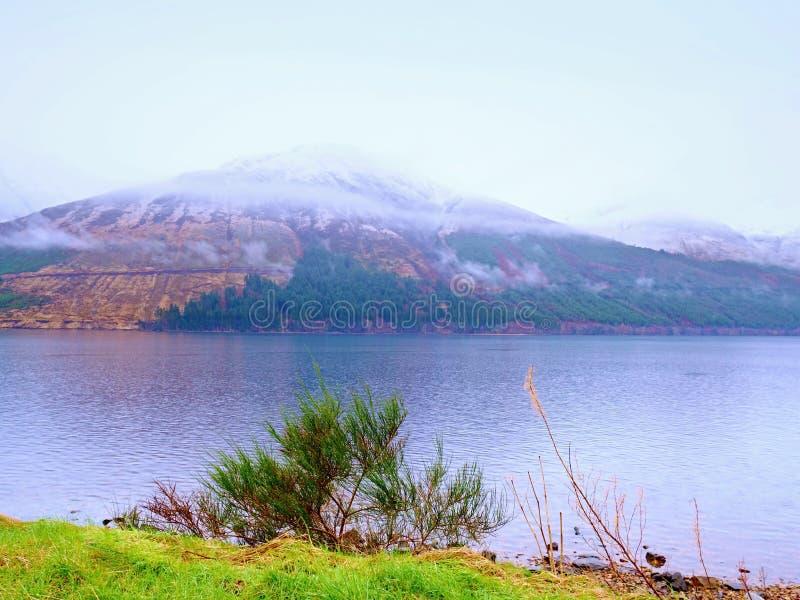 Paisaje de la primavera con las montañas y el lago nevosos Nubes bajas foto de archivo libre de regalías