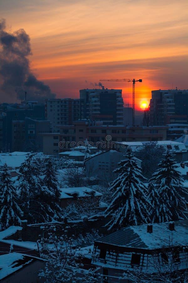 Paisaje de la puesta del sol de la ciudad con los edificios y los árboles en el invierno imágenes de archivo libres de regalías