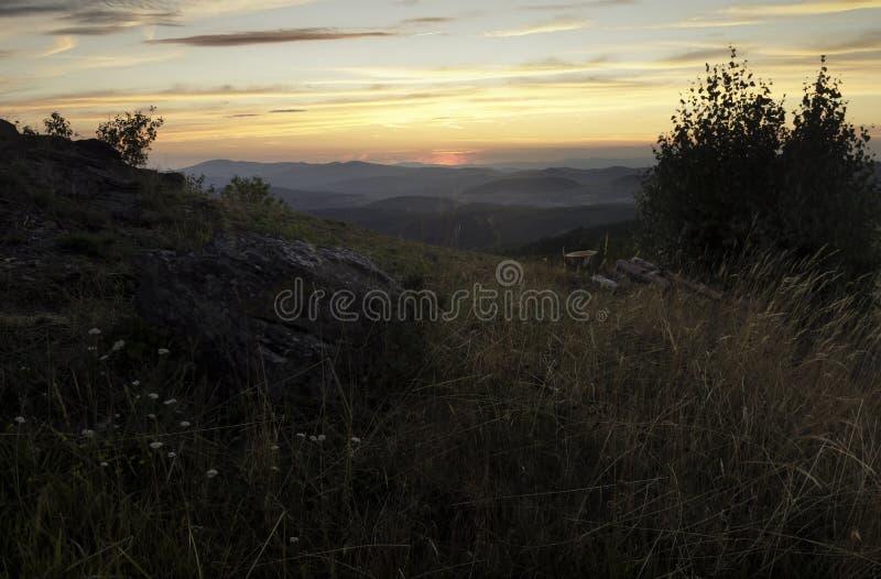 Paisaje de la puesta del sol con la roca grande en primero plano foto de archivo
