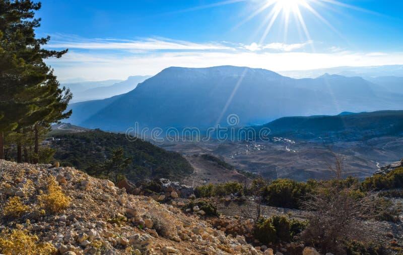 Paisaje de las altas montañas con el cielo azul y el sol salida del sol detrás de las montañas fotografía de archivo libre de regalías
