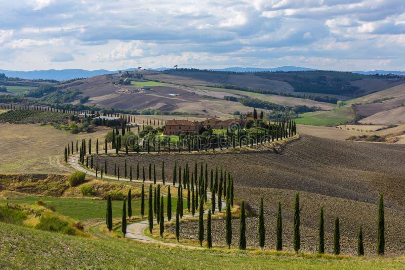 Paisaje de las colinas, de la carretera nacional, de los árboles de cipreses y de las casas rurales, Toscana imagen de archivo