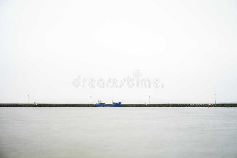 Paisaje de Minimalistic de un embarcadero y de dos botes pequeños fotos de archivo