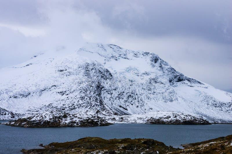 Paisaje de monta?as nevosas y del cielo nublado en Noruega en verano foto de archivo