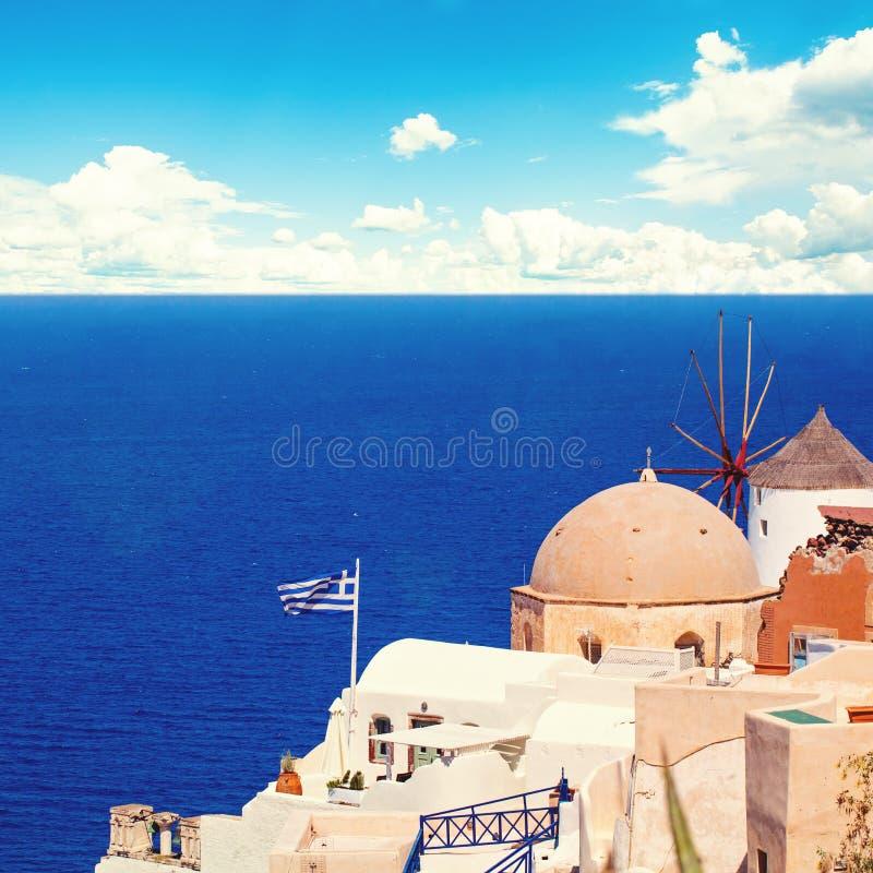Paisaje de Santorini con la bandera griega, las casas blancas, el mar y el cielo azul imagen de archivo