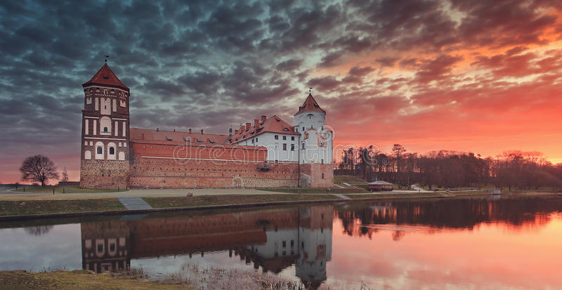 Paisaje de un castillo viejo de Mirsky contra un cielo colorido en un amanecer hermoso imagenes de archivo