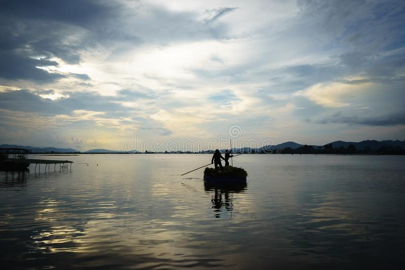 Paisaje de Vietnam El lago con un barco hecho de la hoja de la lona para llevar cosechó el arroz en la puesta del sol imágenes de archivo libres de regalías