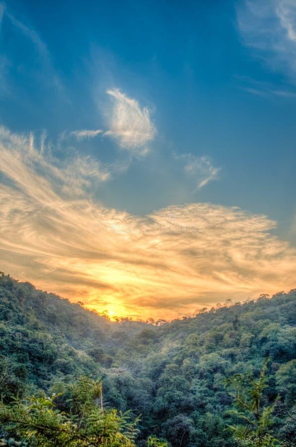 Paisaje del bosque de la montaña debajo del cielo de la tarde con las nubes en luz del sol Imagen de HDR imagen de archivo libre de regalías