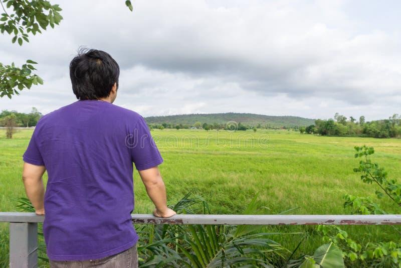 Paisaje del bosque verde con la parte posterior del viajero turístico del hombre asiático en la montaña imagen de archivo