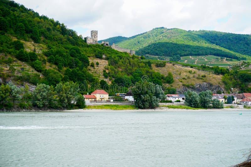 Paisaje del campo con el río, las montañas y las ruinas del castillo cerca de edificios del pueblo fotografía de archivo