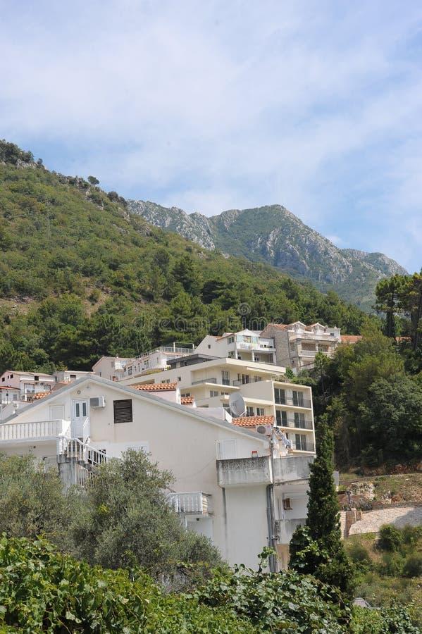 Paisaje del centro turístico - el edificio de apartamentos contra la perspectiva de las montañas y de los cielos azules, Monteneg imagen de archivo
