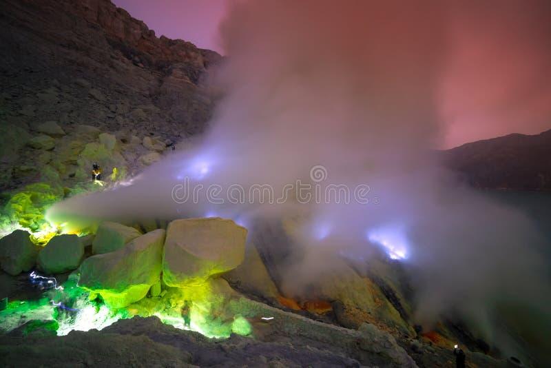 Paisaje del cráter del volcán de Kawah Ijen con la llama azul y de la opinión sulfúrica del humo con mañana del amanecer de la sa foto de archivo