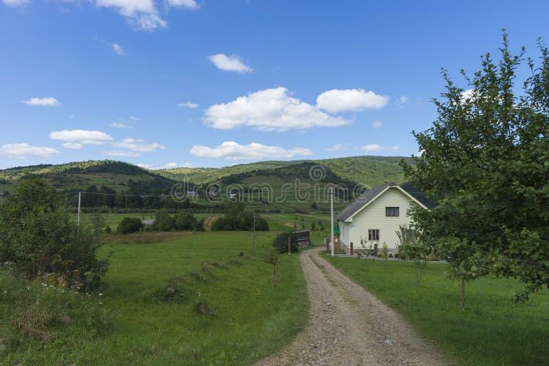 Paisaje del día de verano con el camino, el cielo nublado y las pequeñas casas Ucrania, cárpata imagen de archivo