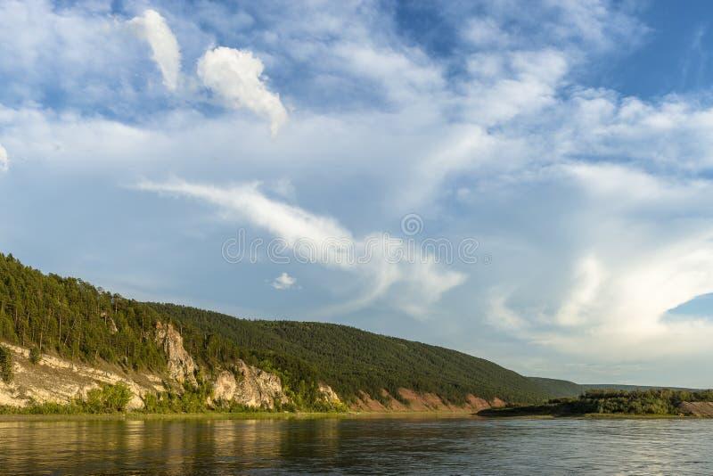 Paisaje del día de verano con el río, el bosque, las nubes en el cielo azul y el sol imagen de archivo libre de regalías