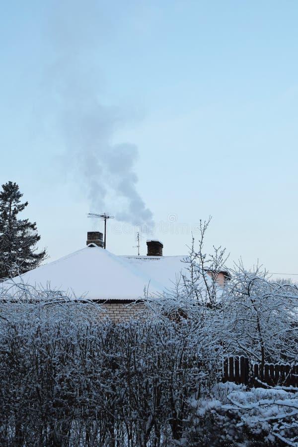 Paisaje del invierno con dos chimeneas ahumadas foto de archivo