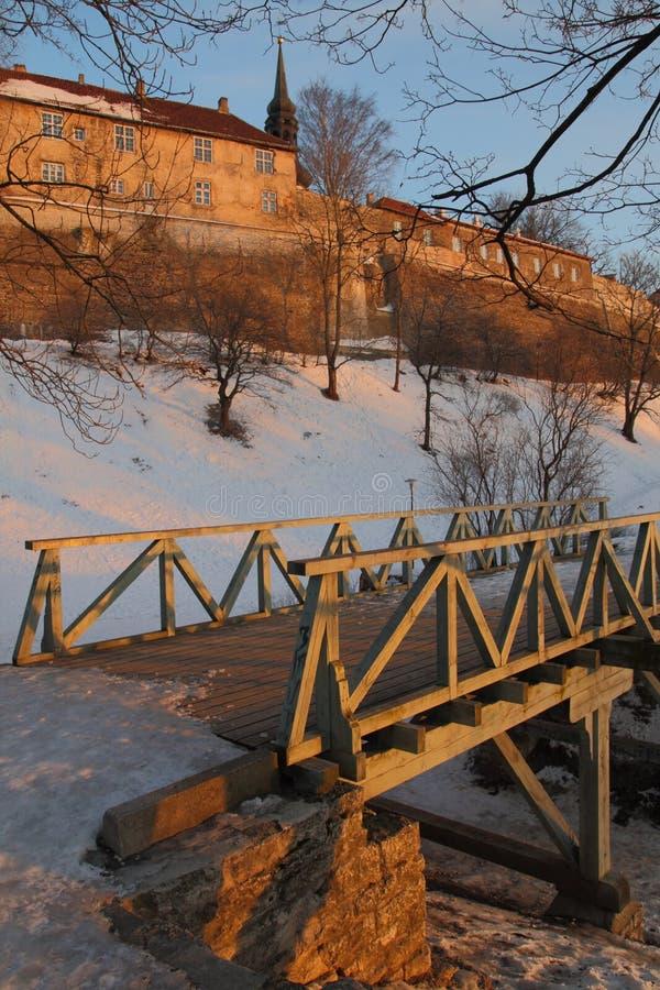Paisaje del invierno con el puente peatonal de madera largo y la ciudad vieja en el fondo imagen de archivo libre de regalías