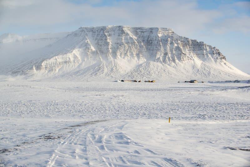 Paisaje del invierno con la montaña, mucha nieve y pequeñas casas de la granja, Islandia fotos de archivo