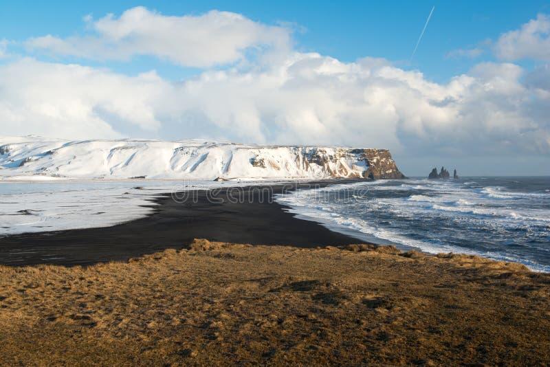 Paisaje del invierno con las montañas, la playa negra y las olas oceánicas, Islandia de la arena imagen de archivo libre de regalías